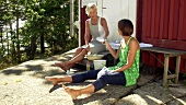 Zwei Frauen beim Geschirr abwaschen vor einem Ferienhaus