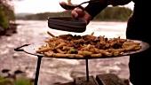 Pfannengericht aus der Feuerschale wird am Fluss serviert