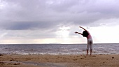 Woman doing Qi Gong exercises by the sea