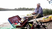 Fishing tackle box, man with beer & grilled fish in background
