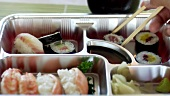 Bento box, dipping maki sushi in soy sauce