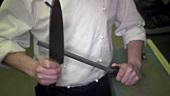 Koch schärft ein Küchenmesser mit dem Wetzstahl