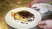 Chef presenting steak with vegetables