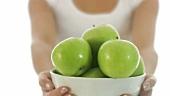 Junge Frau hält eine Schale mit grünen Äpfeln