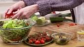 Tomaten auf den Salat geben