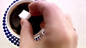 Putting a sugar cube into a cup of coffee