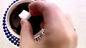 Einen Würfelzucker in eine Tasse Kaffee geben