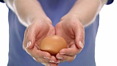 Hands holding a brown egg