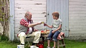 Grandfather and grandson having lunch outside garden shed