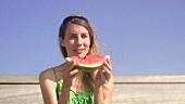 Frau isst Wassermelone im Freien