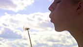 Woman blowing a dandelion clock