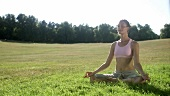 Woman in lotus position in a pasture
