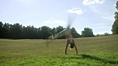 Woman doing cartwheels in park