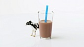 A glass of chocolate milk with straw and a toy cow