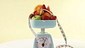 Fresh fruit and tape measure on kitchen scales