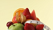 Fresh fruit on kitchen scales, tape measure