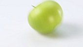 A Granny Smith apple rolling on a white background