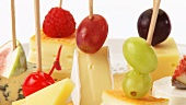 Cheese and fruit on cocktail sticks on crackers