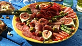 Plate of antipasti: salami, ham, figs, olives, asparagus