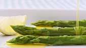 Pouring melted butter over green asparagus