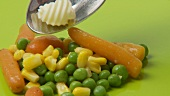 Carrots, peas, sweetcorn with butter curl on green background