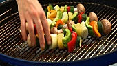 Putting vegetable kebabs on a barbecue