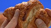 Ein Stück vom Croissant abbrechen