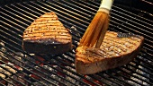 Brushing tuna steaks on a barbecue with marinade