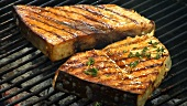 Sprinkling swordfish steaks on a barbecue with herbs