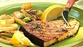 Sprinkling grilled swordfish steak with lemon juice