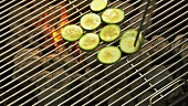 Putting courgette slices on a barbecue