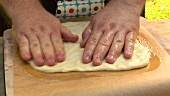 Spreading out pizza dough on baking parchment