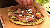 Ziegenkäse auf Pizza verteilen
