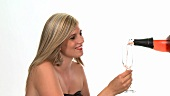 Blond woman with a glass of rosé sparkling wine