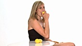 Blond woman biting into a lemon