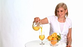 Blond woman drinking a glass of orange juice