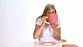 Blond woman drinking out of a giant cup
