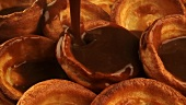 Pouring gravy over Yorkshire puddings
