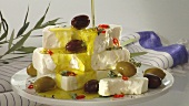 Pouring olive oil over feta and olives