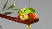 Olivenöl über Tomaten und Mozzarella gießen