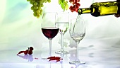 Pouring white wine into glass, glass of red wine, grapes, autumn leaves