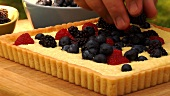 Putting fresh berries on cheese tart