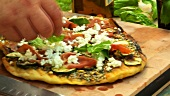 Putting basil leaves on a pizza
