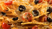 Nachos with olives, tomatoes and melted cheese