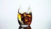 Ice cube falling into a glass of whisky