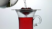Pouring water onto fruit tea in strainer