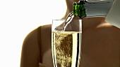 Ein Glas Sekt mit Himbeere einschenken und trinken