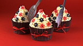 Three cupcakes decorated with sugar flowers and silver dragees