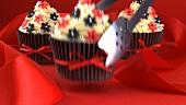 Drei Cupcakes mit Zuckerblüten und Silberperlen verziert
