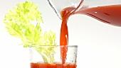 Tomatensaft in ein Glas mit einer Selleriestange gießen